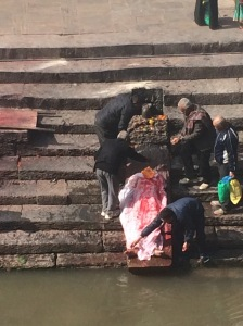 Ritual cleansing of a corpse outside a Hindu temple in Katmandu.